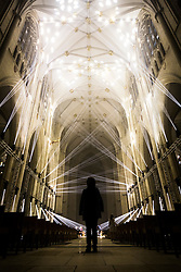 © Licensed to London News Pictures. 26/10/2016. York UK. A lady stands in the middle of the York Minster nave at a preview of Jason Bruges art work, Light Masonry. The artwork has been installed as part of the Illuminating York festival & involves a light projection of 48 beams of light in a synchronised pattern within the nave of York Minster. Illuminating York runs from the 26th to the 29th of October Photo credit: Andrew McCaren/LNP