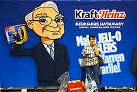A shareholder enjoys a snack under an image of Berkshire Hathaway CEO Warren Buffett at the shareholder shopping day as part of the Berkshire Hathaway annual meeting weekend in Omaha, Nebraska May 5 2017. REUTERS/Rick Wilking