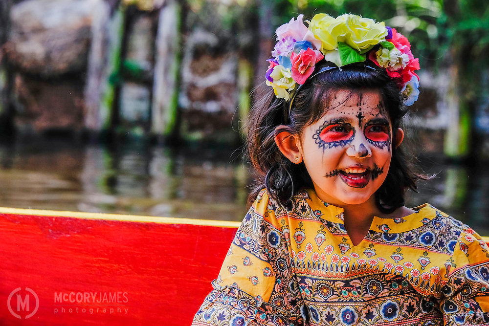 A young girl rides on a gondola on Xochimilco canals during Dia de los Muertos