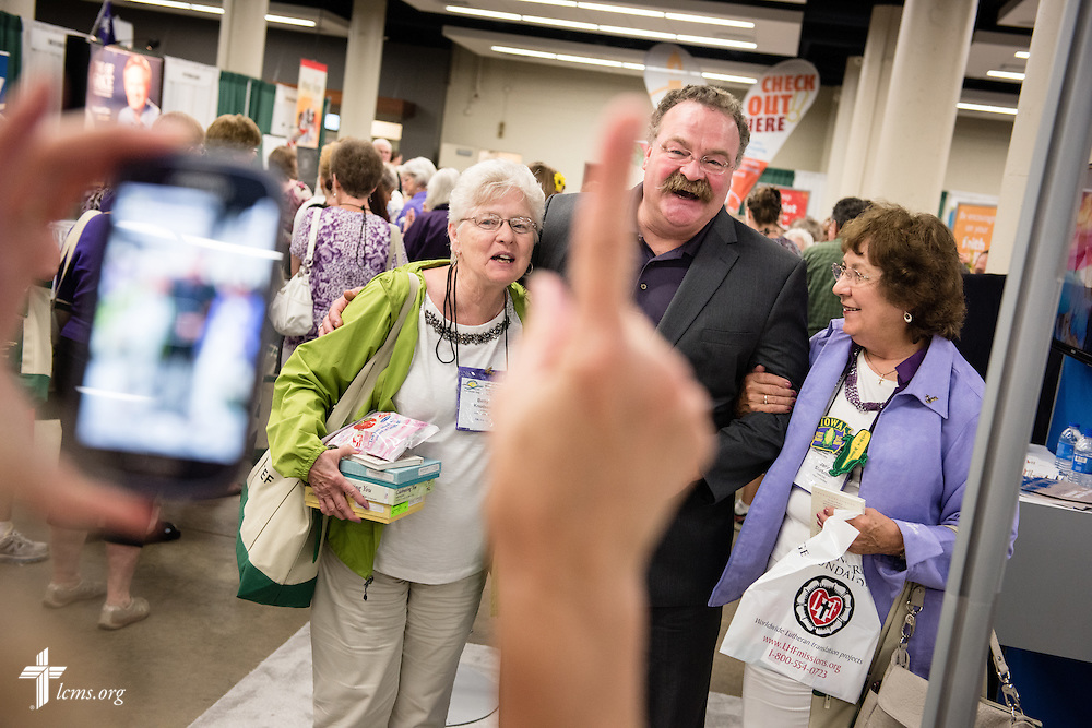 The Rev. Dr. Matthew C. Harrison, president of The Lutheran Church–Missouri Synod, has his photograph made with Betty Knudsen (left) and Janice Shirbroun in the exhibit hall of the 36th Biennial Convention of the Lutheran Women's Missionary League on Friday, June 26, 2015, at the Iowa Events Center in Des Moines, Iowa. LCMS Communications/Erik M. Lunsford