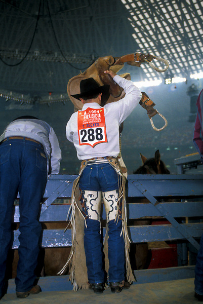 Cowboy saddling his horse at the Houston Livestock Show and Rodeo