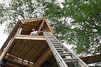 Builder Bob Cosco gets a birds eye view from the deck of the tree house he's building on Riverside Court in Laconia.  (Karen Bobotas/for the Laconia Daily Sun)