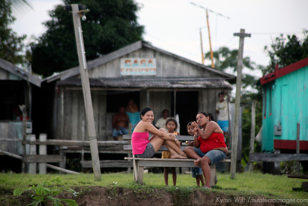 South America, Brazil, Amazon. Girls on a bench watch life pass on the Amazon River.