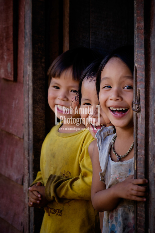 Three children smiling and laughing in a village near Luang Namtha in Northern Laos.