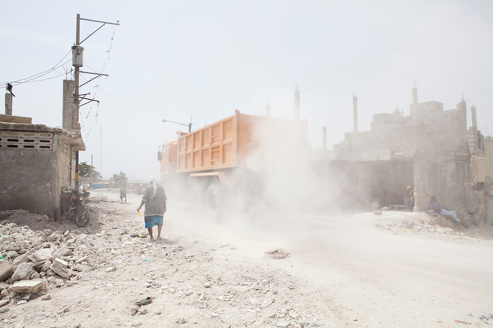 A dump truck kicks up dust as it passes through in the Fort National neighborhood on July 12, 2010 in Port-au-Prince, Haiti.