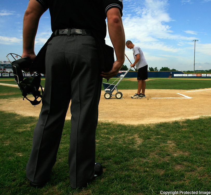 The home plate umpire waits as the batters box is chalked before a recent Clarinda A's game at Municipal Stadium.  photo by David Peterson
