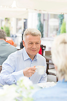 Smiling middle-aged man having coffee with woman at sidewalk cafe