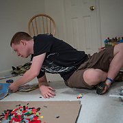 ROCKVILLE, MD - JUL25: John Bucknam, 18, who has autism, puts together a LEGO house at his home in Rockville, MD, July 25, 2014. The Bucknam's have a series of locks on their doors to keep John from wandering off. (Photo by Evelyn Hockstein/For The Washington Post)