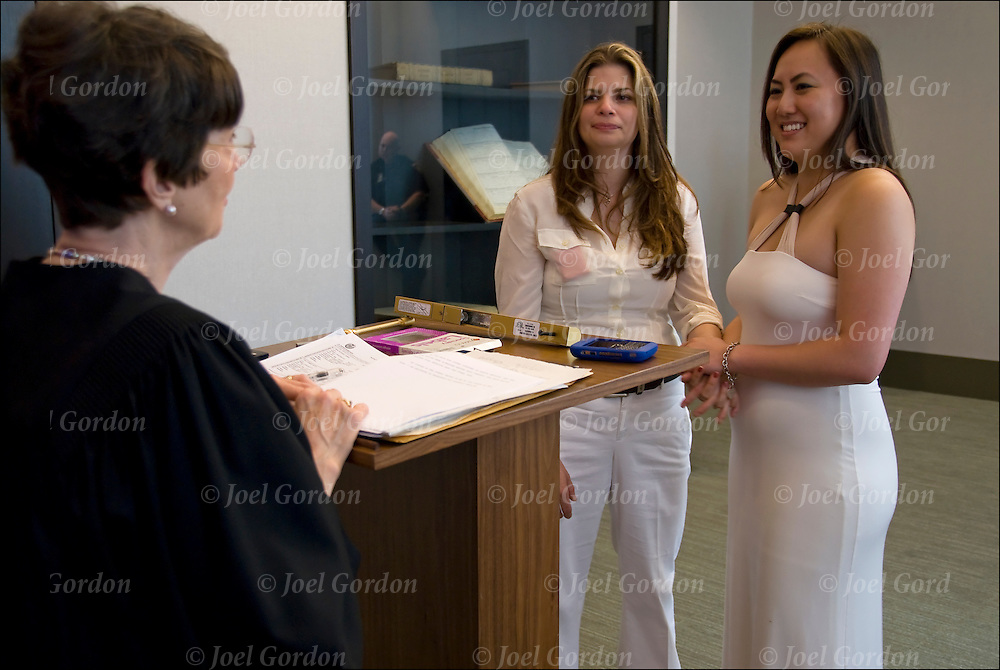 Mixed race ( Caucasian and Asian American ) lesbian couple dressed in white inside City Clerk's Office exchanging their marriage vows.<br /> <br /> Gay marriage became the law, as 484 couples lined up as early as  7 am, outside the City Clerk's Office in lower Manhattan to take their marriage vows.<br /> <br /> Same-sex marriage in the U.S. state of New York became legal on July 24, 2011 under the Marriage Equality Act, which was passed on June 24, 2011 by the New York State Legislature and signed by Governor Andrew Cuomo on the same day.<br /> <br /> The Marriage Equality Act does not have a residency restriction like some other states and allows religious organizations to decline from officiating same sex wedding ceremonies.