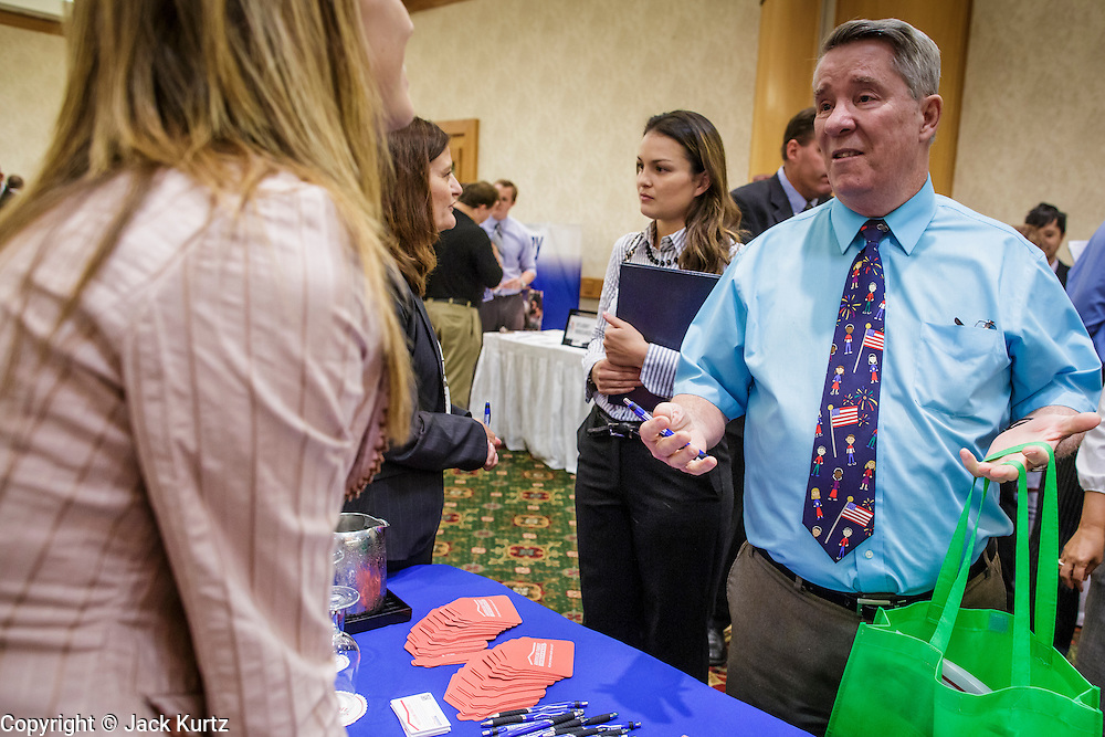 30 JULY 2012 - PHOENIX, AZ:   ANGIE MUNIZ, from American Family insurance, talks to GARY GOLONKA, a job seeker, at the Phoenix Job Fair in Phoenix, AZ. The job fair was sponsored by National Career Fairs, which organizes job fairs across the US. Several hundred people attended the job fair, with some arriving hours before it started. More than 30 employers and prospective employers were conducting interviews at the job fair. There were also resume coaches and educational institutions on site. Arizona is still grappling with the recession. The state's unemployment rate is stuck at 8.2% and the Phoenix metropolitan area has one of the highest home foreclosure rates in the United States.    PHOTO BY JACK KURTZ