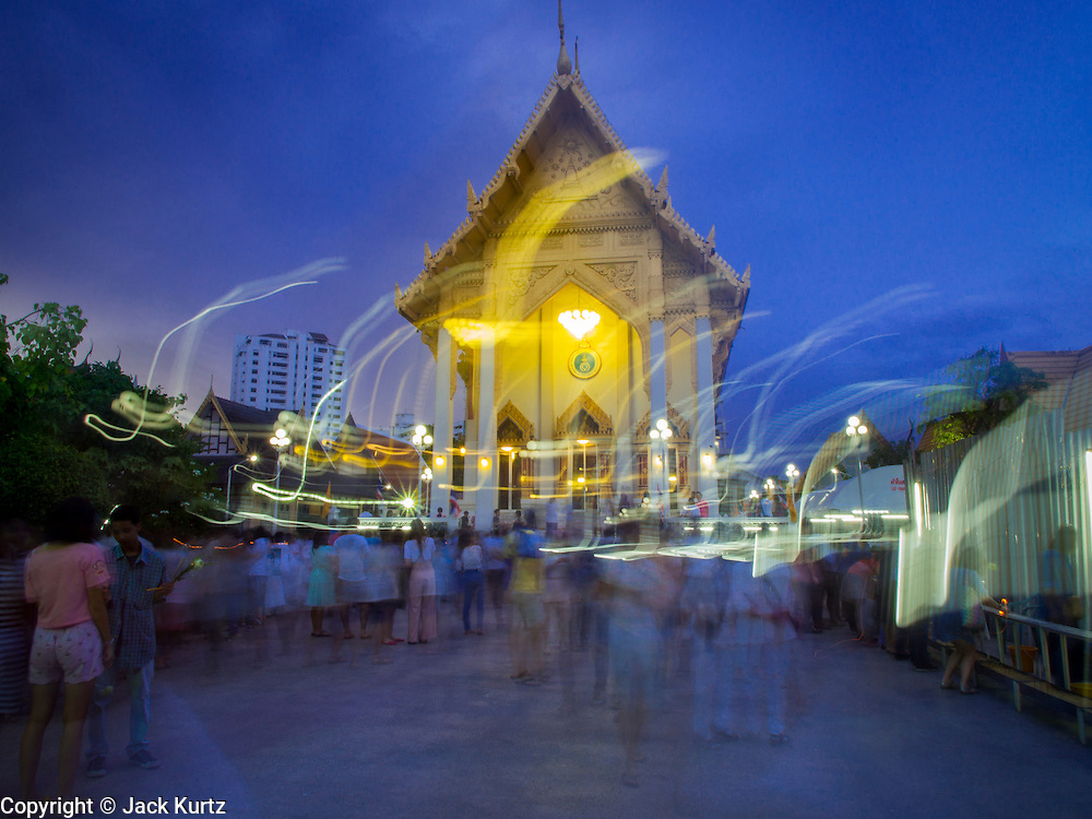 """13 MAY 2013 - BANGKOK, THAILAND: People gather for Vesak on the plaza in front of Wat That Thong in Bangkok. Vesak, called Wisakha Bucha in Thailand, is one of the most important Buddhist holy days celebrated in Thailand. Sometimes called """"Buddha's Birthday"""", it actually marks the birth, enlightenment (nirvana), and death (Parinirvana) of Gautama Buddha in the Theravada or southern tradition. It is also celebrated in Cambodia, Laos, Myanmar, Sri Lanka and other countries where Theravada Buddhism is the dominant form of Buddhism.     PHOTO BY JACK KURTZ"""