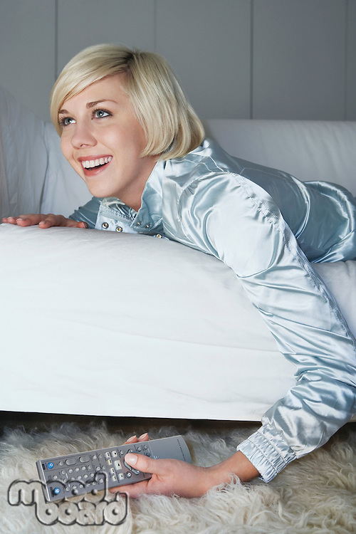 Woman lying on sofa holding remote control laughing