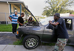 20 August 2015. New Orleans, Louisiana. <br /> Hurricane Katrina revisited. <br /> August Turner (rt) has friends come over to help repair his car. A decade later and recovery remains largely elusive for the area hardest hit by Katrina.<br /> Photo credit©; Charlie Varley/varleypix.com.