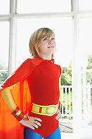 Portrait of young boy (7-9) in superhero costume hands on hip indoors