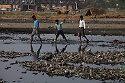 Three Indian boys are crossing the heavily polluted and semi-dry Yamuna River next to the Taj Mahal, in Agra.