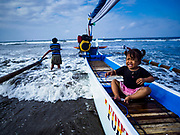 29 JULY 2017 - AIRKUNING, BALI, INDONESIA: A child sits in her family's outrigger fishing canoe while her father tries to bring it in to shore after a night fishing in Airkuning, a Muslim fishing village on the southwest corner of Bali. The child did not go out with her father. She and her mother were waiting on shore for him when he came in. Villagers said their regular catch of fish has been diminishing for several years, and that are some mornings that they come back to shore with having caught any fish.    PHOTO BY JACK KURTZ