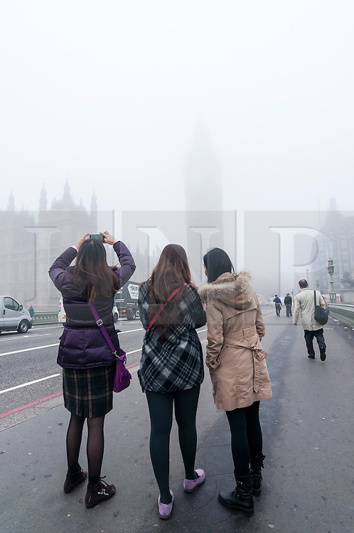 © Licensed to London News Pictures. 02/11/2015. London, UK. Commuters arriving for work after the half-term holiday are met with a blanket of thick fog over the Houses of Parliament as they cross Westminster Bridge.  Photo credit : Stephen Chung/LNP