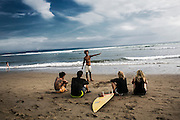 BALI, INDONESIA; APRIL 17, 2015: A surf instructor explains about surfing to students at Batubolong beach, Bali, Indonesia, on Friday, April 17, 2015.