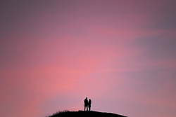 © Licensed to London News Pictures. <br /> 29/12/2014. <br /> <br /> Saltburn, United Kingdom.<br /> <br /> A couple stand on top of a hill called Cat Nab at Saltburn by the Sea in Cleveland as the pink skies of evening light up the sky and temperatures drop below freezing as the cold weather continues.<br /> <br /> Photo credit : Ian Forsyth/LNP
