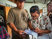06 OCTOBER 2016 - BANGKOK, THAILAND:  A woman who accepted Bangkok city money and moved out Pom Mahakan signs papers stating the she is moving out of the old fort and that her home will be destroyed. Evictions are continuing at a slow pace in Pom Mahakan Fort and as people move out their homes are destroyed to ensure new squatters don't move in. More than 40 families still live in the Pom Mahakan Fort community. Bangkok officials are trying to move them out of the fort and community leaders are barricading themselves in the fort. The residents of the historic fort are joined almost every day by community activists from around Bangkok who support their efforts to stay. City officials said recently that they expect to have the old fort cleared of residents and construction on the new park started by the end of 2016.     PHOTO BY JACK KURTZ
