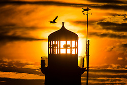 © Licensed to London News Pictures. 12/02/2019. Scarborough UK. The sun rises behind Scarborough lighthouse this morning on the Yorkshire coast. Photo credit: Andrew McCaren/LNP