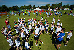 LIVERPOOL, ENGLAND - Wednesday, June 18, 2014: A coach teaches children as they attempt a world record for the largest ever tennis lesson during Kids Day of the Liverpool Hope University International Tennis Tournament at Liverpool Cricket Club. (Pic by David Rawcliffe/Propaganda)