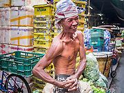 08 JANUARY 2013 - BANGKOK, THAILAND:   A porter poses for portraits in the Bangkok Flower Market. The Bangkok Flower Market (Pak Klong Talad) is the biggest wholesale and retail fresh flower market in Bangkok. It is also one of the largest fresh fruit and produce markets in the city. The market is located in the old part of the city, south of Wat Po (Temple of the Reclining Buddha) and the Grand Palace.    PHOTO BY JACK KURTZ