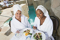 Portrait of women in bathrobes eating by pool