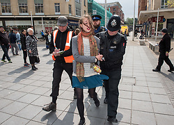 © Licensed to London News Pictures. 04/05/2017. Bristol, UK. A woman is arrested on suspicion of writing slogans using chalk on the pavement at an anti-fracking protest. Activists from 'Rising Up' lock themselves together with their arms in a tube on top of Barclays Bank in Broadmead shopping centre. Police removed the two protestors with help from the fire brigade's turntable ladder, and both rooftop protestors were arrested plus another person was arrested on suspicion of writing slogans using chalk on the pavement. The protest is a prelude to Global Divestment in Fossil Fuels day on Friday 05 May and 06 May. Photo credit : Simon Chapman/LNP