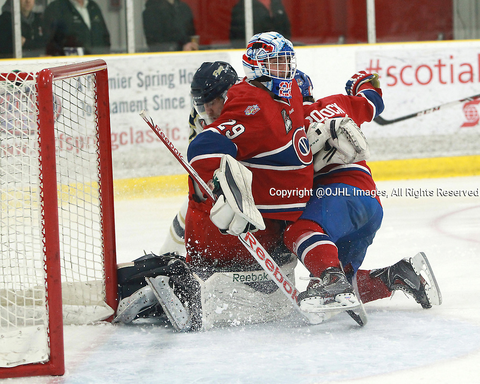 TORONTO, ON - Apr 15, 2015 : Ontario Junior Hockey League game action between the Toronto Patriots and the Kingston Voyageurs. Game Three of the Buckland Cup Championship Series. Daniel Urbani #29 of the Kingston Voyageurs makes the save as Mike Crocock #18 crashes into the net with the Patriot player in the first period.<br /> (Photo by Tim Bates / OJHL Images)