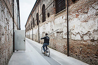 VENICE, ITALY - 1 MAY 2017: A worker carries a pole by bike at the Arsenale,  an exhibition venue of the 57th International Art Exhibition, one week before the inauguration in Venice, Italy, on May 1st 2017.<br /> <br /> The 57th International Art Exhibition, titled VIVA ARTE VIVA and curated by Christine Macel, is organized by La Biennale di Venezia chaired by Paolo Baratta. VIVA ARTE VIVA will unfold over the course of nine chapters or families of artists, beginning with two introductory realms in the Central Pavilion, followed by another seven across the Arsenale through the Giardino delle Vergini. 120 are the invited artists from 51 countries; 103 of these are participating for the first time. <br /> <br /> The Exhibition will also include 85 National Participations in the historic Pavilions at the Giardini, at the Arsenale and in the historic city centre of Venice. 3 countries will be participating for the first time: Antigua and Barbuda, Kiribati, Nigeria.