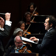"""November 21, 2013 - New York, NY : Conductor Alan Gilbert, left, leads the New York Philharmonic and tenor Dominic Armstrong, at right, in Bejamin Britten's """"Spring Symphony, Op. 44 (1948-49)"""" at Avery Fisher Hall at Lincoln Center on Thursday night. Armstrong made his NY Phil debut as a last-minute substitution for tenor Paul Appleby, who withdrew due to illness. CREDIT: Karsten Moran for The New York Times"""