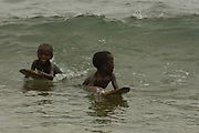 Antandroy children body-surfing in the waves with home-made boogie board made from wood.  Lavanono fishing village, south coast of MADAGASCAR