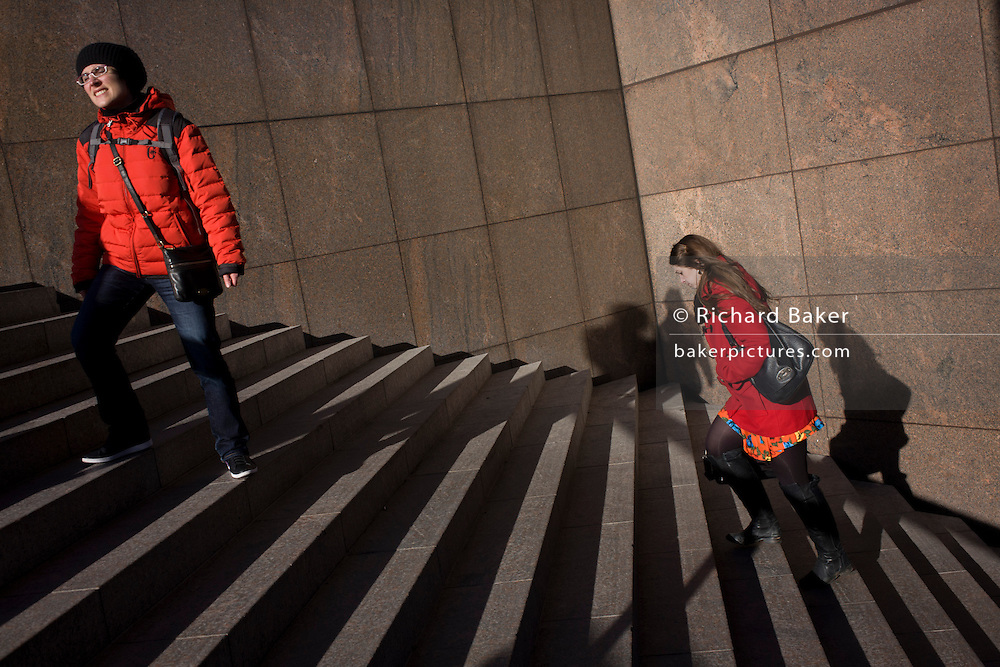 Two women both in red stand and climb city steps.