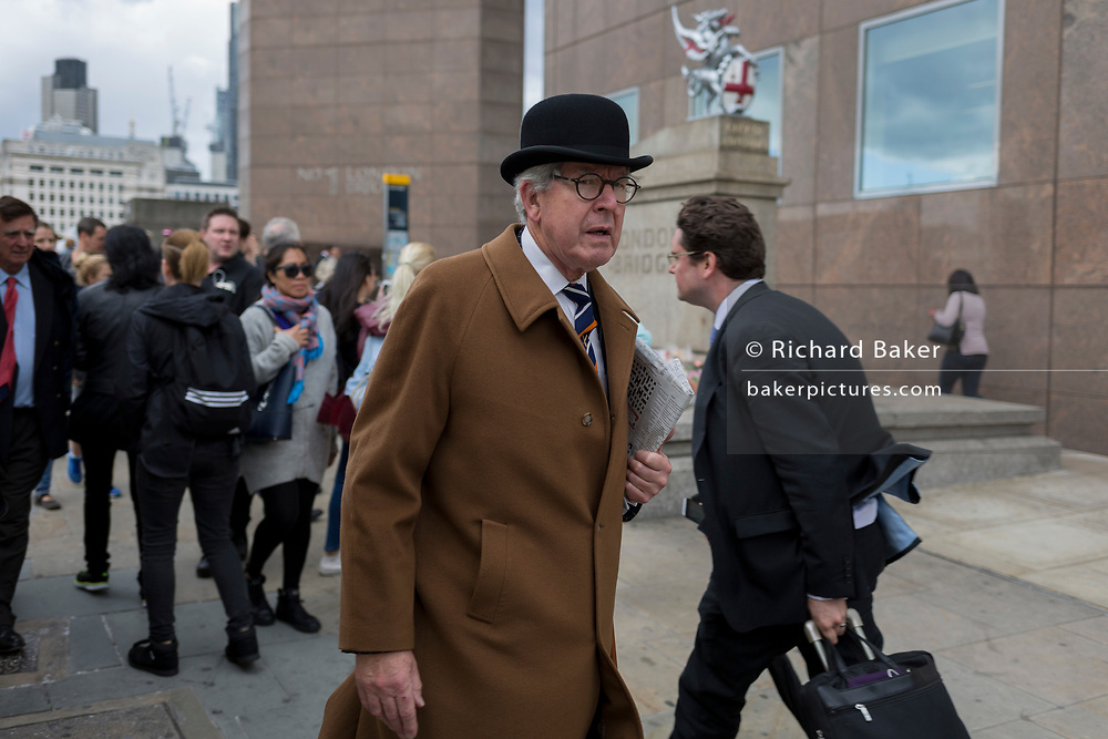 A city gent wearing a traditional but now a very rarely-seen bowler hat walks over London Bridge with other commuters, on 6th June 2017, on London Bridge, in the south London borough of Southwark, England. The griffin behind him is on the southern end of the Thames crossing but marks the southern boundary of the City of London, the capital's financial district.