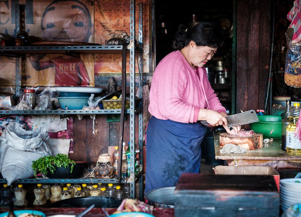 KYAING TONG, MYANMAR - CIRCA DECEMBER 2017:  Burmese woman cooking at her restaurant in the Loi Mwe Hill Village. Shan State around Kyaing Tong in Myanmar.