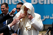 Security officers try to adjust Pope Benedict XVI's frock after the wind caught it during a welcoming ceremony at the Mount Scopus helipad in Jerusalem, Monday, May 11, 2009.