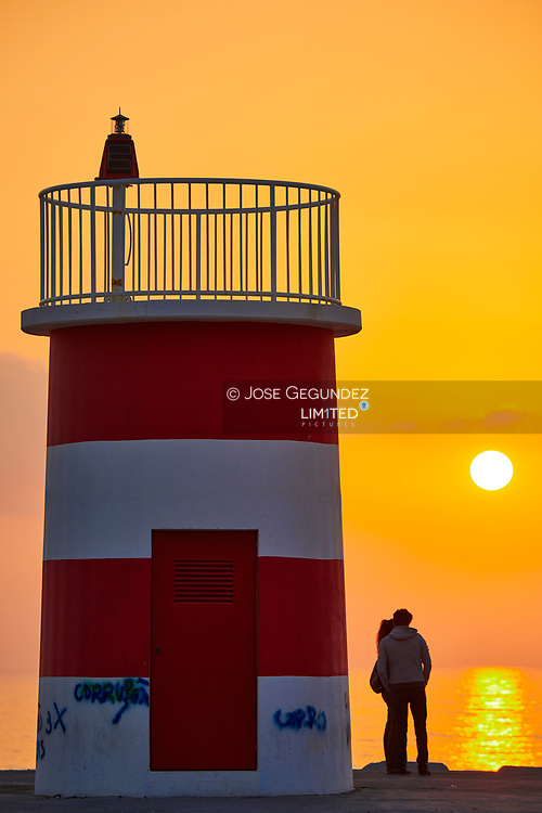 A couple in a lighthouse at sunset in Nazare, Portugal