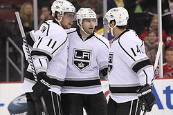 Oct 13; Newark, NJ, USA; Los Angeles Kings center Anze Kopitar (11) and Los Angeles Kings right wing Justin Williams (14) celebrate a goal by Los Angeles Kings left wing Simon Gagne (12) during the first period at the Prudential Center.