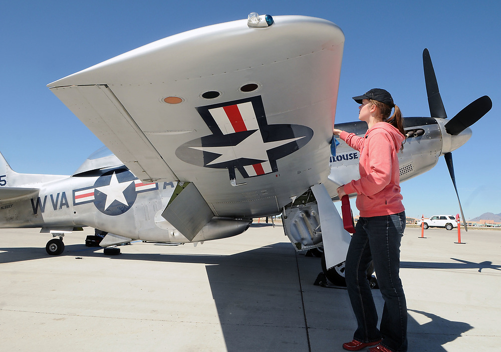 jt040517b/a sec/jim thompson/  Roxanne Parker cleans up the North American TF-51D Mustang on the Cutter Aviation tarmac as the four planes of the Wings of Freedom Tour is in Albuquerque Wednesday April 5th-7th.  April 05, 2017. (Jim Thompson/Albuquerque Journal)