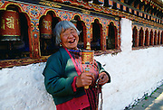 An old woman with prayer wheels laughing at the Kyichu Buddhist Temple in Paro, Bhutan