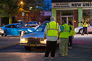 Bellmore, New York, USA. August 11, 2017.  Members of the Chamber of Commerce of the Bellmores and Nassau County Auxiliary Police wear yellow neon reflective safety vests as they guide cars into the main lot of the Long Island Rail Road Bellmore Train Station parking lot where the Bellmore Friday Night Car Show is held.