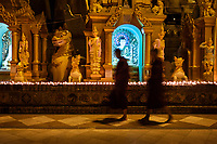 YANGON, MYANMAR - CIRCA DECEMBER 2017: Monks walking at the Shwedagon Pagoda in Yangon at night