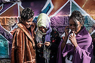 Three Eritrean girls calling, with a shared smartphone, their families left in Africa and their friends already arrived in Germany.