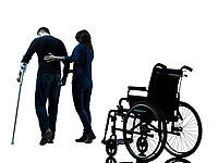 one man injured man with woman walking away from wheelchair with crutches in silhouette studio on white background