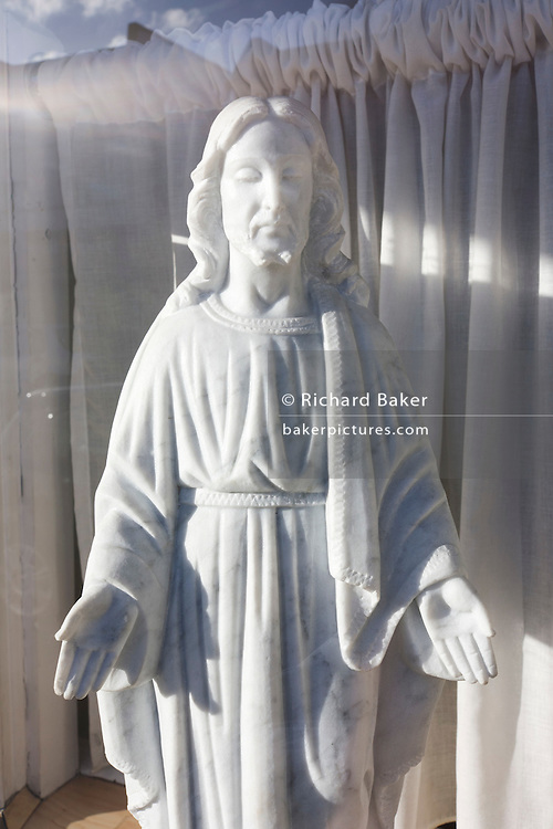 A small statuette of Jesus stands in bright sunlight in a funeral parlour's front window.