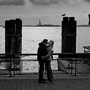 Couple kissing in front of the Statue of Liberty