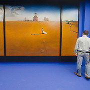 "MILAN, ITALY - SEPTEMBER 21:  A man and a woman admire ""Landscape with girl skipping rope"", oil painting by Salvador Dali at the Exhibition preview at Palazzo Reale on September 21, 2010 in Milan, Italy. Dali is back in Milan with Il sogno si avvicina, an exhibition that takes place at Palazzo Reale  and that focus on the relationship between the great Spanish artist's visions and his favourite themes:  landscape, dream and desire."