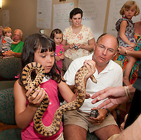 "Katie and Stan Rogers get an up close and personal look at a bull snake during Gilford Library's ""Reptiles on the Move"" presented by Marie Leighton and her assistant Robert Breslin Tuesday afternoon.  (Karen Bobotas/for the Laconia Daily Sun)Reptiles on the Move at Gilford Library."