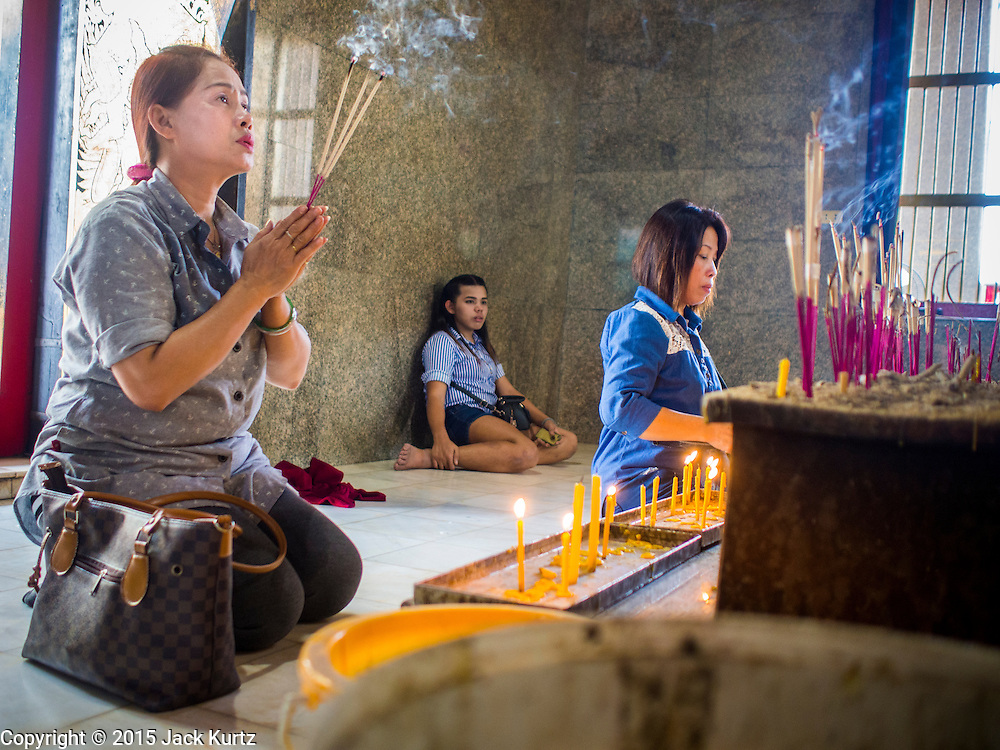 05 JANUARY 2015 - THONBURI, BANGKOK, THAILAND:  People pray in a memorial to King Taksin the Great at Wat Intharam, an Ayutthaya period temple in the Thonburi section of Bangkok. Wat Intharam was reportedly the favorite temple of King Taksin the Great, the Thai King credited with reunifying Siam (Thailand) after the Burmese sacked the ancient capital of Ayutthaya in 1767 CE. Taksin established the new Thai capital city in Thonburi, which is closer to the ocean and more easily defended, and made Wat Intharam his personal favorite. He was cremated at Wat Intharam following his death in 1782. His ashes are at the temple. There is a memorial to King Taksin the Great at the back of the temple grounds.    PHOTO BY JACK KURTZ